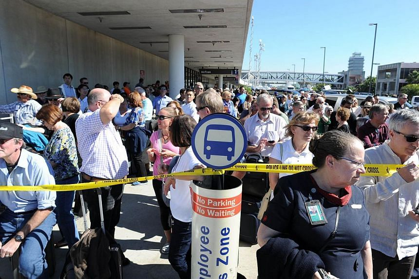 Delayed passengers and others wait behind police lines after a shooting at Los Angeles International Airport (LAX) on Nov 1, 2013. -- PHOTO: REUTERS