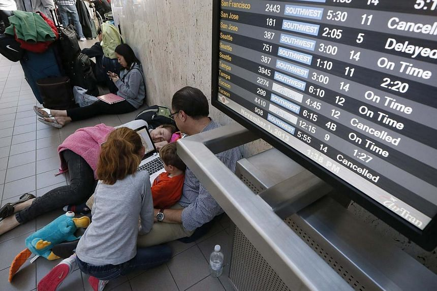 Jacqueline Klee, 37, sleeps in the terminal after her flight to Mexico was delayed after a shooting at Los Angeles airport (LAX), California, Nov 1, 2013. -- PHOTO: REUTERS