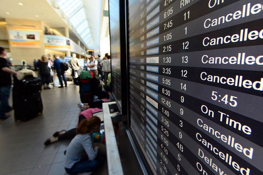 A board shows many flights have been cancelled or delayed inside Terminal 1 at Los Angeles International Airport (LAX) on Nov 1, 2013 after a gunman reportedly opened fire at a security checkpoint. -- PHOTO: AFP