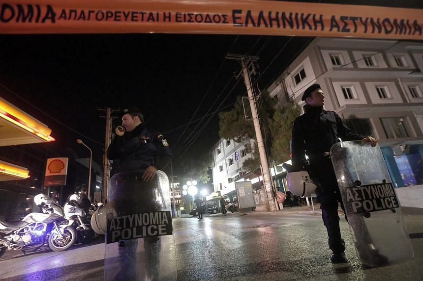 Police officers stand guard near the local offices of far-right Golden Dawn party, following a shooting, in a northern suburb of Athens, Nov 1, 2013. Two men were killed and another person seriously injured Friday in a shooting outside the Athens par