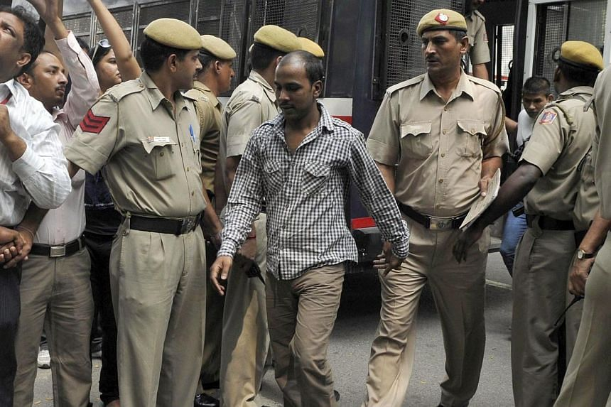 Mukesh Singh (centre), one of the four men who were sentenced to death for the rape and murder of a young woman on a bus last December, is escorted by police outside a court in New Delhi, on Sept 24, 2013. A court in New Delhi has begun hearing appea