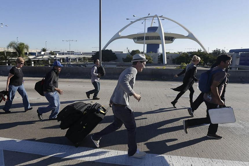 People run towards Terminal 2 at Los Angeles International Airport on Nov 1, 2013, after the terminal was reopened. The Los Angeles International Airport terminal where a gunman opened fire on Friday morning, killing an unarmed federal airport securi