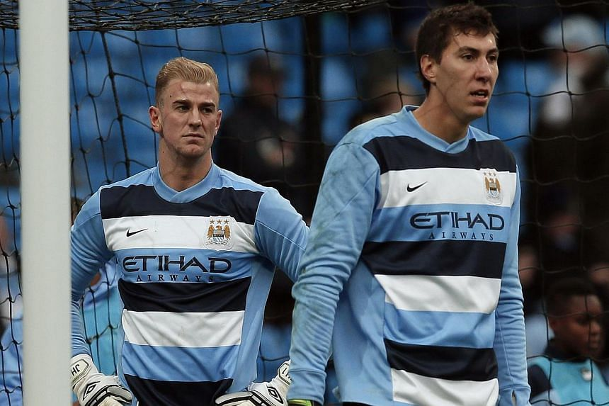 Manchester City's goalkeepers Joe Hart (left) and Costel Pantilimon warm up ahead of their English Premier League soccer match against Norwich City at the Etihad Stadium in Manchester, northern England on Nov 2, 2013. -- PHOTO: REUTERS