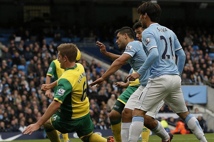 Manchester City's Sergio Aguero (centre) shoots, resulting in a Manchester City goal, during their English Premier League soccer match against Norwich City at the Etihad Stadium in Manchester, northern England on Novr 2, 2013. -- PHOTO: REUTERS