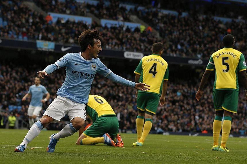 Manchester City's David Silva (left) celebrates after scoring his side's second goal during their English Premier League soccer match against Norwich City at the Etihad Stadium in Manchester, northern England on Nov 2, 2013. -- PHOTO: REU