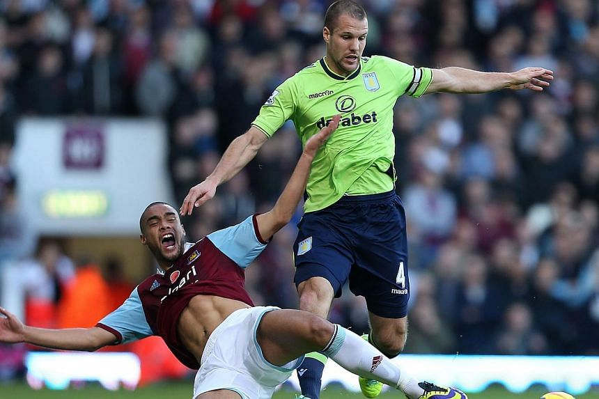 West Ham United's Winston Reid and Aston Villa's Ron Vlaar compete for the ball during the English Premier League match at Upton Park, London on Saturday, Nov 2, 2013.West Ham avoided a fourth consecutive home defeat with a goalless draw