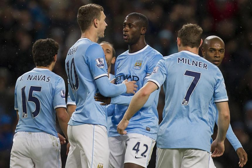 Manchester City's Edin Dzeko, centre left, celebrates with teammates including Yaya Toure, centre right, after scoring his side's 7th goal against Norwich during their English Premier League soccer match at the Etihad Stadium, Manchester, England, on