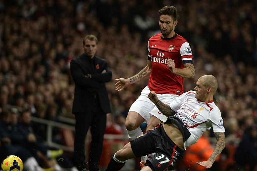 Arsenal's Olivier Giroud (left) challenges Liverpool's Martin Skrtel during their English Premier League soccer match at the Emirates stadium in London on Nov 2, 2013. -- PHOTO: REUTERS