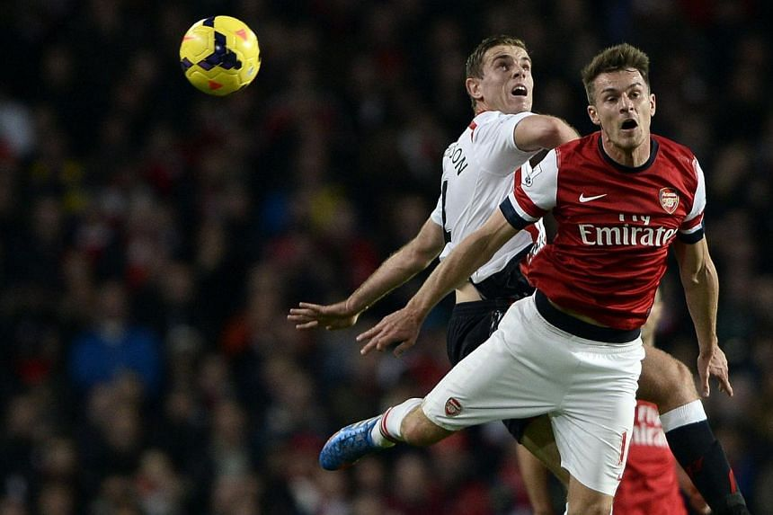 Arsenal's Aaron Ramsey (right) challenges Liverpool's Jordan Henderson during their English Premier League soccer match at the Emirates stadium in London on Nov 2, 2013. -- PHOTO: REUTERS