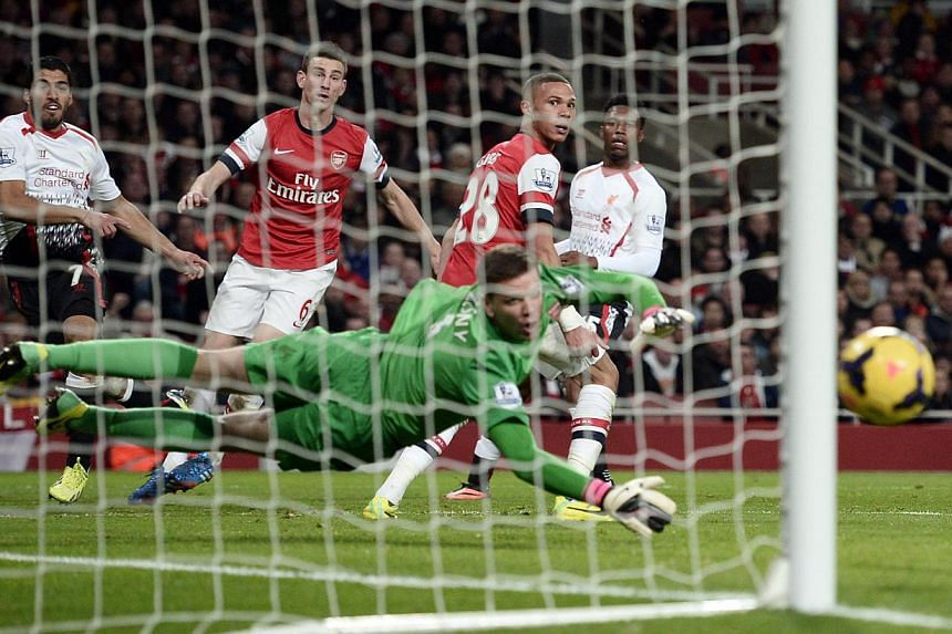 Liverpool's Luis Suarez (left) shoots and hits the post during their English Premier League soccer match against Arsenal at the Emirates stadium in London on Nov 2, 2013. -- PHOTO: REUTERS