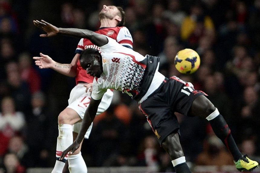 Arsenal's Olivier Giroud challenges Liverpool's Mamadou Sakho (front) during their English Premier League soccer match at the Emirates stadium in London on Nov 2, 2013. -- PHOTO: REUTERS