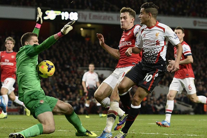 Arsenal's Wojciech Szczesny (left) saves a shot from Liverpool's Philippe Coutinho (R) during their English Premier League soccer match at the Emirates stadium in London on Nov 2, 2013. -- PHOTO: REUTERS