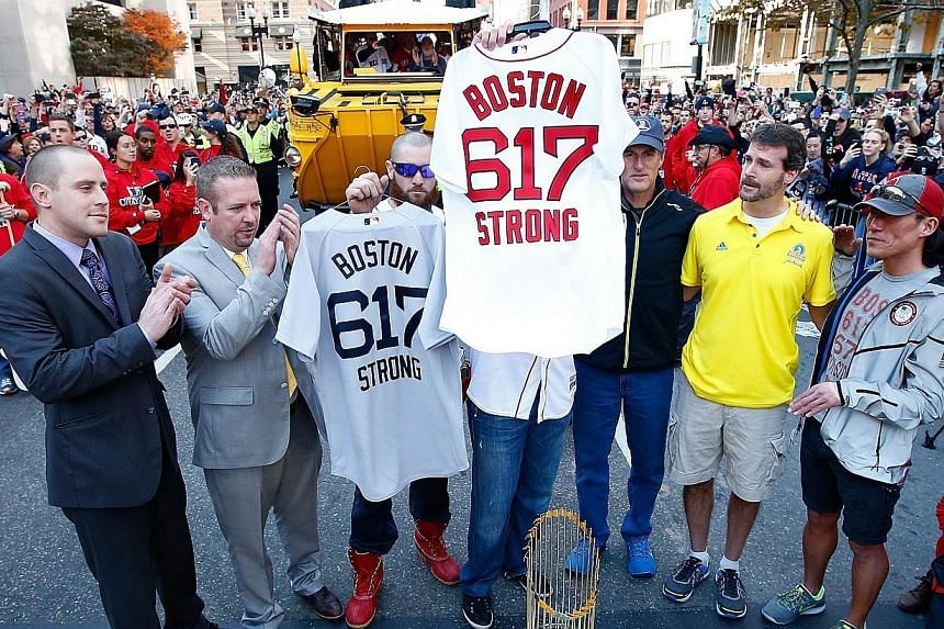 Jonny Gomes #5 and Jarrod Saltalamacchia #39 of the Boston Red Sox present the 'Boston Strong 617' jerseys to owners of two of the businesses at the bombing sites, including Shane O'Hara (second from right) and Dan Solo (right) on the finish line of