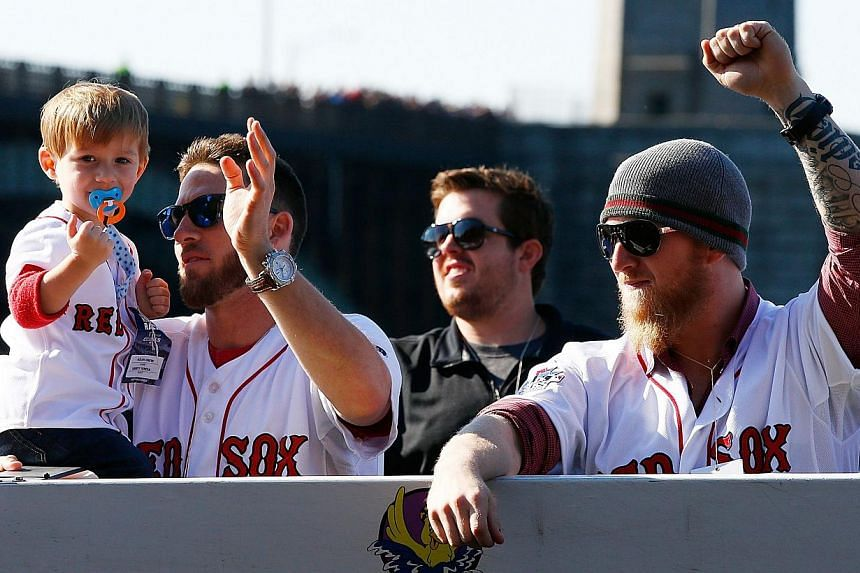 Stephen Drew #7 and Mike Carp #37 of the Boston Red Sox celebrate on the Charles River during the World Series victory parade on Nov 2, 2013 in Boston, Massachusetts. -- PHOTO: AFP