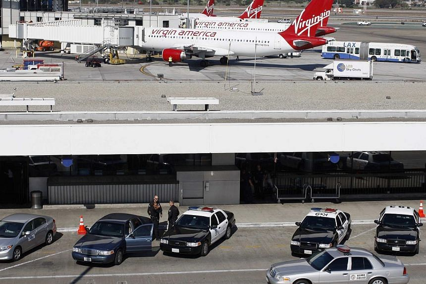 Law enforcement vehicles are seen under a lot where passenger jets are parked, at the gates of Terminal 3 the day after a shooting incident at Los Angeles airport (LAX), California on Nov 2, 2013. The gunman who opened fire at the airport, killing on
