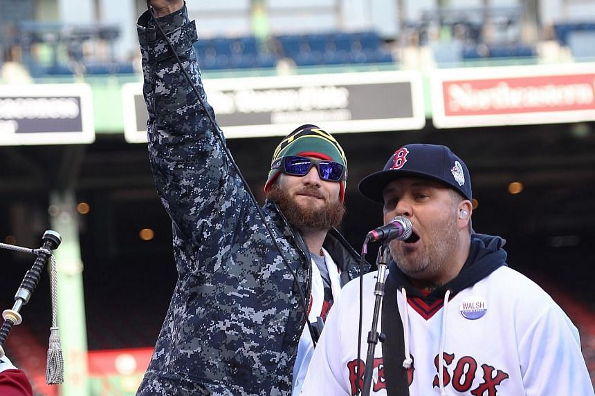 Jonny Gomes (left) and Ken Casey of the Drop Kick Murphys perform for the crowd before the Red Sox players board the duck boats for the World Series victory parade for the Boston Red Sox on Nov 2, 2013 in Boston, Massachusetts. -- PHOTO: AFP