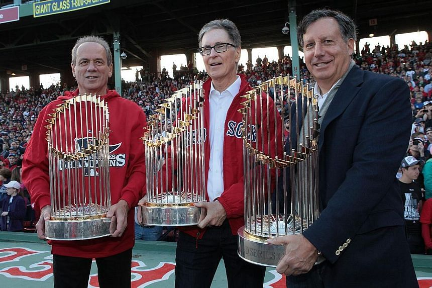 President and CEO of the Boston Red Sox Larry Lucchino, (left), Red Sox principal own John Henry (center), and Red Sox chairmanTom Werner show off the World Series trophies to the crowd at Fenway Park before the Red Sox players board the duck boats f