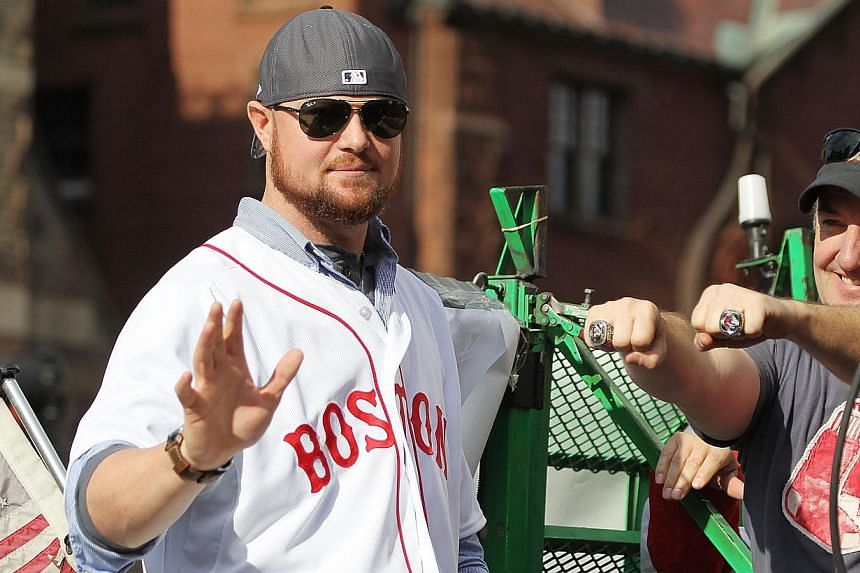 Jon Lester waves from one of the duck boats as they make their way down Boylston Street where fans gathered for the World Series victory parade for the Boston Red Sox on Nov 2, 2013 in Boston, Massachusetts. -- PHOTO: AFP