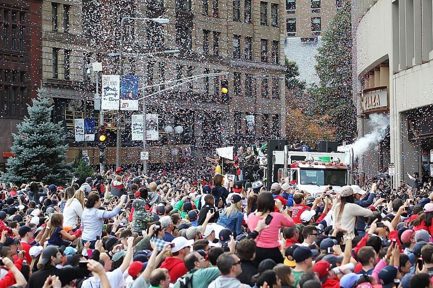 The crowd at Boston City Hall Plaza cheers as the duck boats make their way down Tremont Street during the World Series victory parade for the Boston Red Sox on Nov 2, 2013 in Boston, Massachusetts. -- PHOTO: AFP