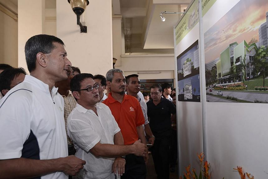 Minister for Environment and Water Resources Dr Vivian Balakrishnan (left) looks at an artist's impression of the Bukit Panjang Hawker Centre after the groundbreaking ceremony held on Nov 3, 2013. Beside him is Toh Kok Soon of sqft Architects.