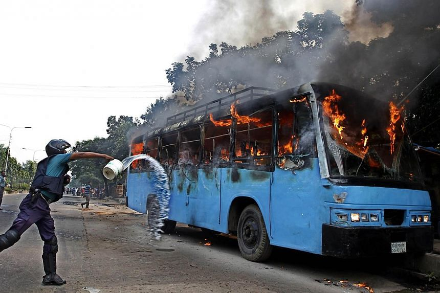 A Bangladesh police-man throws water at a bus set alight during a protest ahead of a three-day strike, in the capital Dhaka, on Nov 3, 2013. Bangladesh police fired rubber bullets and tear gas at opposition protesters Sunday before the start of anoth