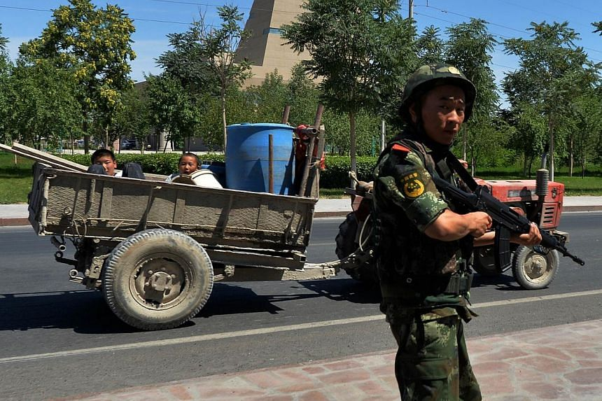 Chinese paramilitary police man a checkpoint on the road to the riot-affected Uighur town of Lukqun, Xinjiang province, on June 28, 2013. China's Communist Party has expelled the military commander of Xinjiang from its ranks, state media reported on