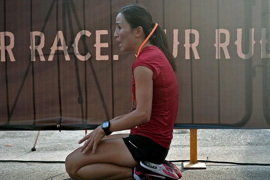 Anne Qi Hui taking a break at the finishing line after winning the age 25 & above female category at the Nike We Run Singapore race held at the F1 Pit Building, on Nov 3, 2013. -- ST PHOTO: KUA CHEE SIONG