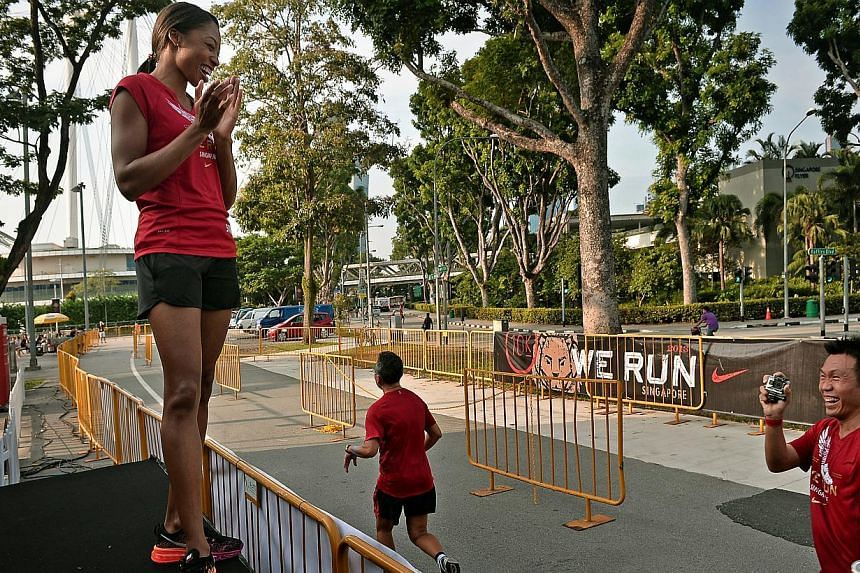 Olympic and world champion Allyson Felix cheering on runners who had decided to run an extra 1.5km after finishing their 10km Nike We Run Singapore race held at the F1 Pit Building, on Nov 3, 2013. -- ST PHOTO: KUA CHEE SIONG