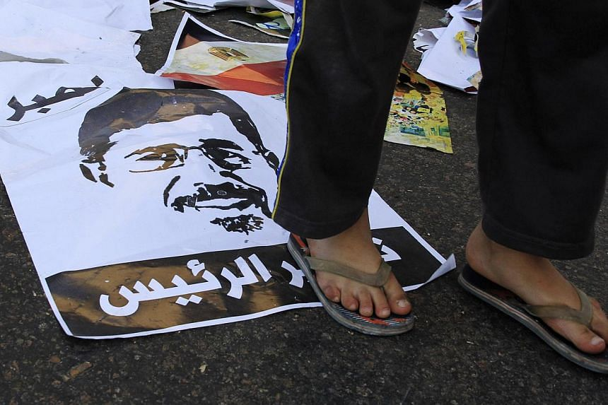 An anti-Mursi protester stands on a picture of deposed President Mohamed Mursi during clashes in Alexandria Nov 1, 2013. Mr Mursi, goes on trial on Monday under a security crackdown that has devastated his Muslim Brotherhood movement and raised conce