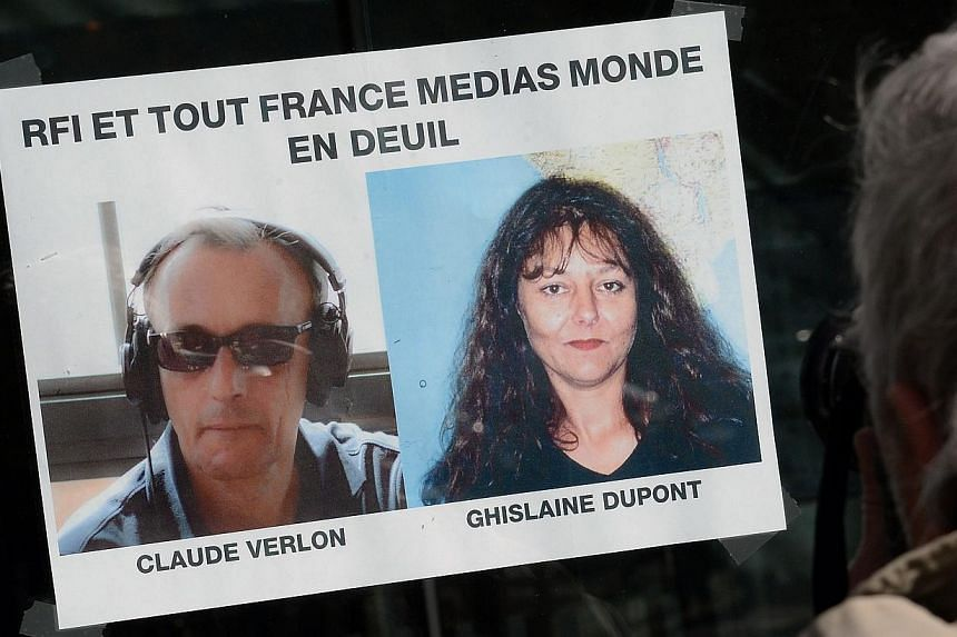 """A man looks at the pictures of late French journalists of French radio station Radio France Internationale (RFI) Ghislaine Dupont and Claude Verlon on a page reading """"RFI and all France Media Monde in mourning"""" in Paris, on Nov 3, 2013. Paris blamed"""