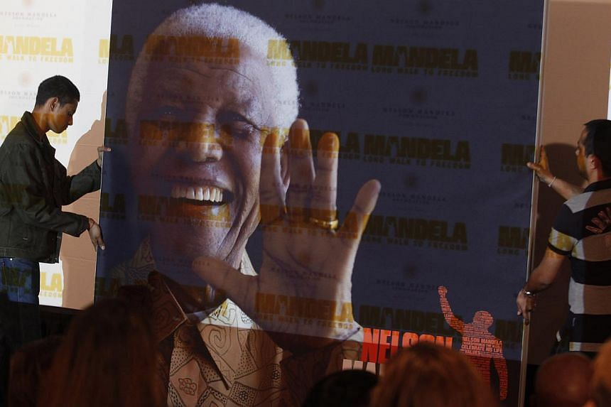 A giant poster of Nelson Mandela is moved to center stage at a news conference held on the eve of the South African premier of the film Mandela - Long Walk To Freedom, in Johannesburg, on Saturday, Nov 2, 2013. -- PHOTO: AP