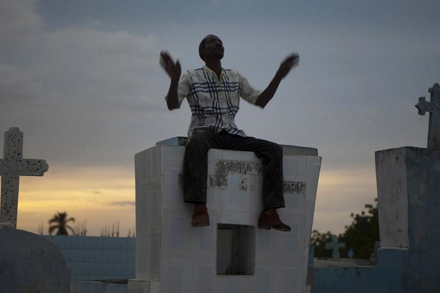 In this Friday, Nov 1, 2013, photo, a voodoo devotee prays while sitting on the headstone of a grave during Day of the Dead celebrations at the cemetery in Port-au-Prince, Haiti. -- PHOTO: AP