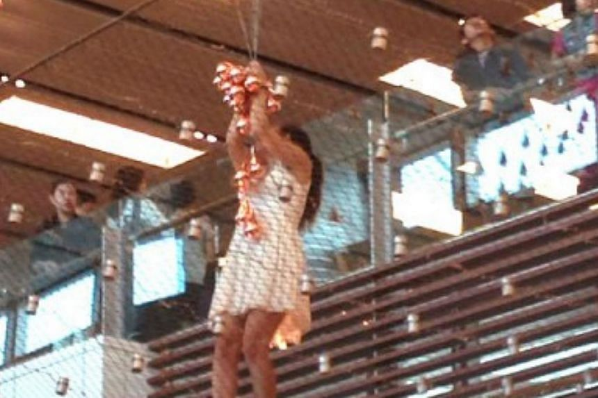 A woman was arrested by the police after she climbed over the railing at Changi Airport Terminal 1 onto the netting below the Kinetic Rain sculpture on Saturday morning.-- PHOTO: STOMP