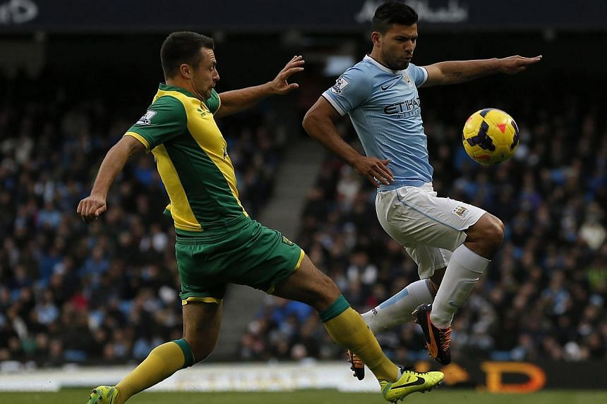 Manchester City's Sergio Aguero (right) challenges Norwich Citys Bradley Johnson during their English Premier League soccer match at the Etihad Stadium in Manchester, northern England on Nov 2, 2013. -- PHOTO: REUTERS
