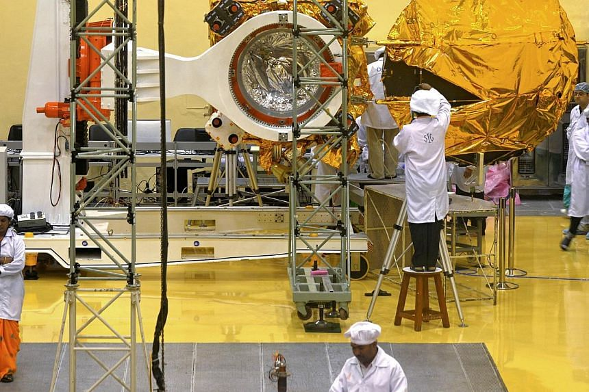 In this file picture taken on Sept 11, 2013, scientists and engineers work on a Mars Orbiter vehicle at the Indian Space Research Organisation's (ISRO) satellite centre in Bangalore in Bangalore.India began a countdown on Sunday to the launch o