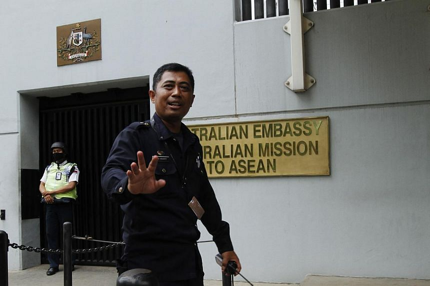 A security personnel raises his hand in an attempt to stop the media from taking pictures in front of the Australian Embassy gate in Jakarta on Nov 1, 2013. -- FILE PHOTO: REUTERS