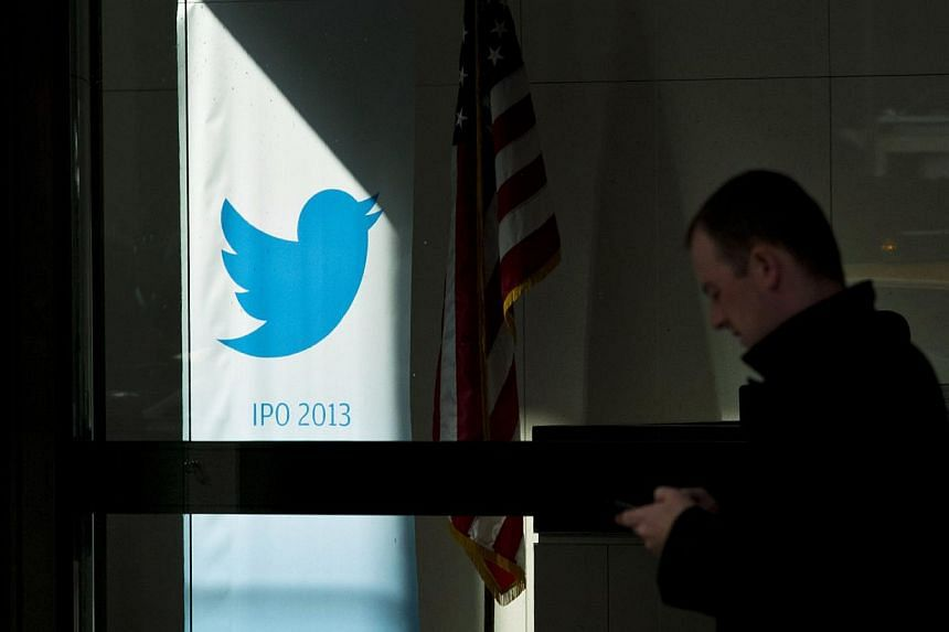 A man walks past a Twitter banner while leaving JP Morgan headquarters, before the firm's IPO in New York, on Oct 25, 2013. -- FILE PHOTO: REUTERS