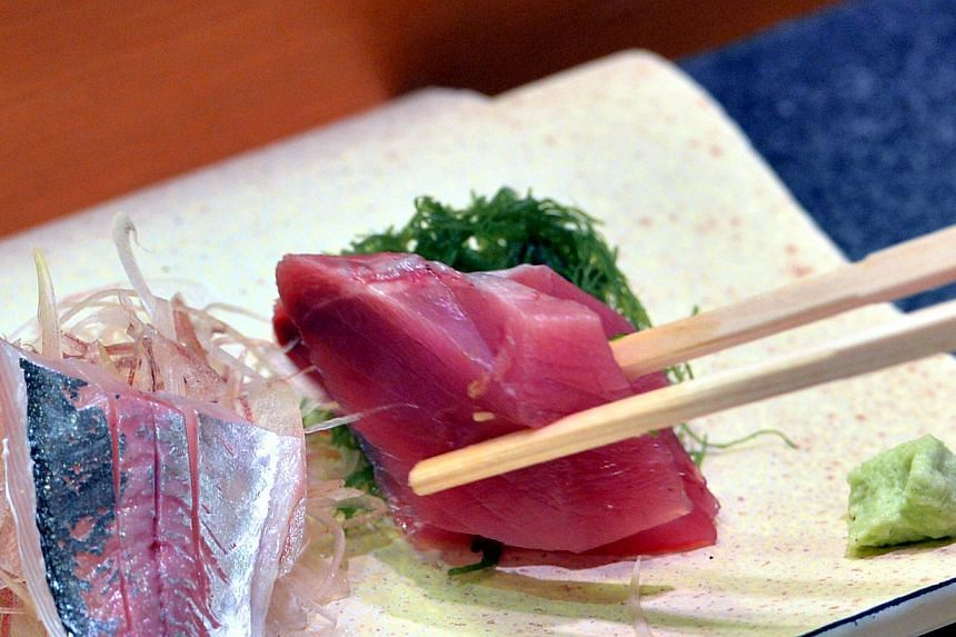 A customer eating sashimi (raw fish) at a high-end sushi restaurant in Tokyo in this file photo taken on July 16, 2013. There have been red faces across Japan since Osaka-based Hankyu Hanshin Hotels (HHH) admitted last month that eight directly-manag