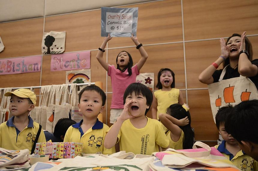 Six-year-old Jazper Quek (centre), selling hand-painted tote bags yesterday with his school mates (from left), Randall Nie and Eron Wong, both six, and his teacherJasmine Mok (far right), 24, in support of Child Aid, which benefits the ST Schoo