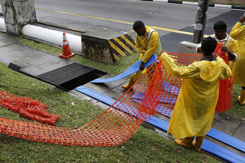 Workers carrying out drainage works in New Upper Changi Road. The PUB said drainage improvement to the flood-pronesection, which also includes part of Chai Chee Road, will be speeded up. -- PHOTO: DESMOND LUI FOR THE STRAITS TIMES
