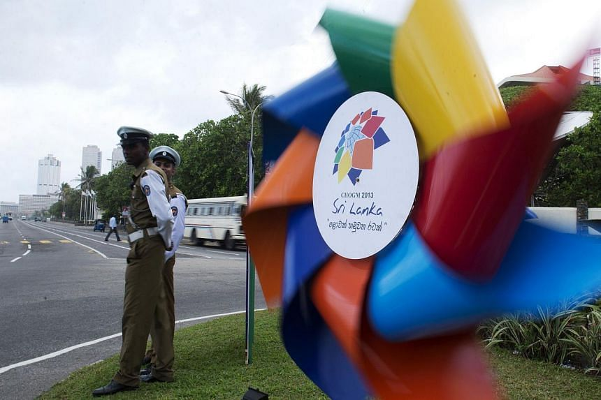 Sri Lankan police officers look at a billboard featuring a windmill announcing the Commonwealth Heads of Government Meeting (CHOGM) in Colombo on Oct 16, 2013.A senior Indian minister on Monday urged Prime Minister Manmohan Singh to boycott a C