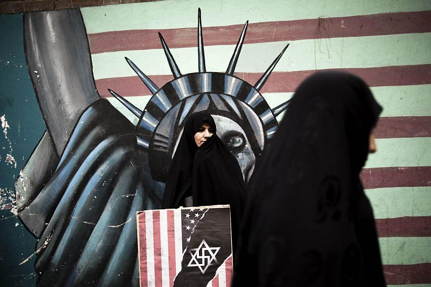 An Iranian woman holds an anti-US poster as she stands in front of a mural of the Statue of Liberty bearing the face of a skull on the wall of the former US embassy in Teheran on Monday, Nov 4, 2013, during a demonstration to mark the 34th anniversar