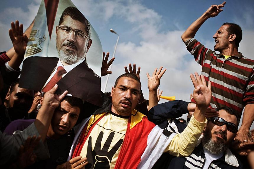 Egyptian supporters of the Muslim Brotherhood or ousted president Mohamed Mursi shout slogans in his support during a protest outside the Police Academy where Mursi's trial takes place on Monday, Nov 4, 2013, in Cairo, Egypt. An Egyptian co