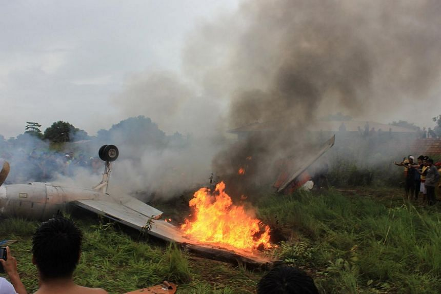 People look at a Fairchild Swearingen Metroliner aircraft of Bolivian airliner Aerocon that crashed on its approach to the Riberalta airport in the Beni Province, on Nov 3, 2013. -- PHOTO: REUTERS