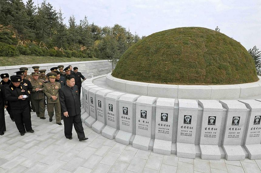 This undated picture released by North Korea's official Korean Central News Agency (KCNA) on November 2, 2013 shows North Korean leader Kim Jong Un (front right) visiting the cemetery of fallen fighters of the KPA Navy Unit 790 at an undisclosed loca