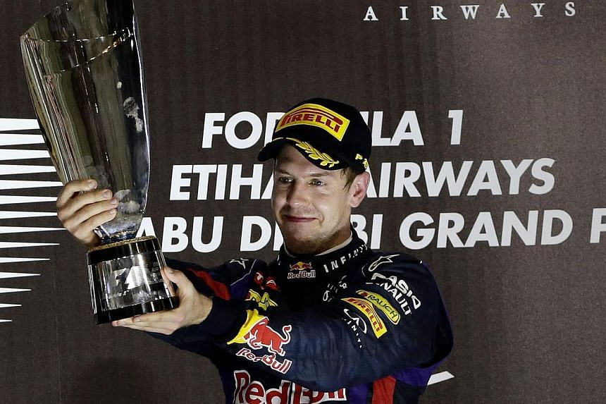 Red Bull driver Sebastian Vettel of Germany holds up the trophy on the podium after winning the Abu Dhabi Formula One Grand Prix at the Yas Marina racetrack in Abu Dhabi, United Arab Emirates, on Nov 3, 2013. Vettel said he does not believe he will b
