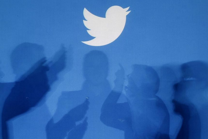 The shadows of people holding mobile phones are cast onto a backdrop projected with the Twitter logo in this illustration picture taken in Warsaw on Sept 27, 2013. Twitter has chosen to trade on the New York Stock Exchange, shunning the rival Nasdaq