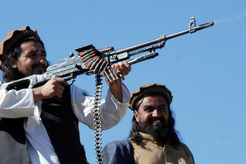 This file picture taken on November 26, 2008, shows Pakistani Taliban commander Hakimullah Mehsud (left) firing from a rifle as he poses for a group of media representatives in the Mamouzai area of Orakzai Agency. The United States implicitly de
