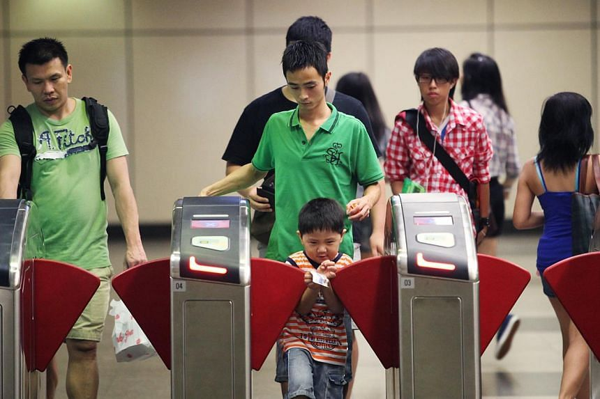 People using their EZ Link card at Braddell MRT station.Up to one million commuters could benefit from new and enhanced concession schemes proposed by a committee reviewing public transport fares. -- ST FILE PHOTO:SAM CHIN