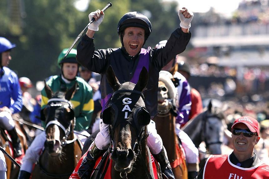 Jockey Damien Oliver (centre), sitting atop race favourite Fiorente, celebrates after winning the A$6 million (S$7 million)Melbourne Cup at Flemington Racecourse in Melbourne on Tuesday, Nov 5, 2013.Fiorente finished strongly to win the M